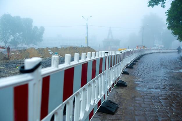 道路補修部のプラスチック柵。霧のかかった天気、