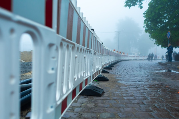 Plastic fencing of the road repair section. foggy weather,