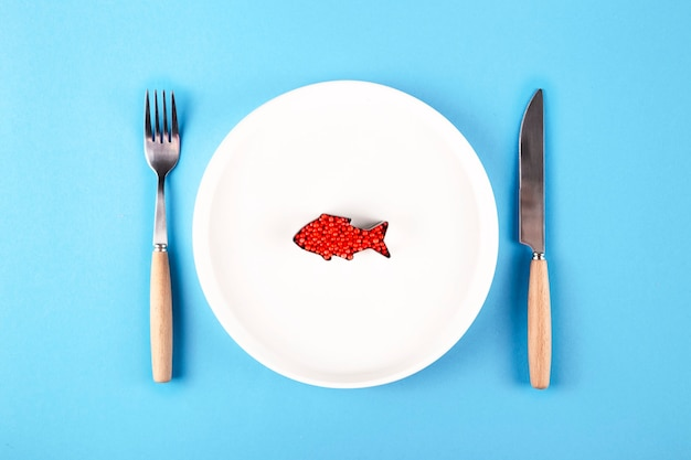 나이프와 포크 옆 접시에 플라스틱 물고기 프리미엄 사진