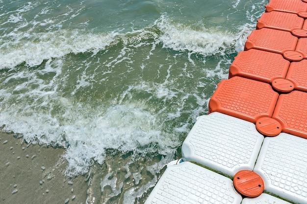 Пластиковая плавающая док-станция, пластиковые понтонные кубики в море в солнечный день