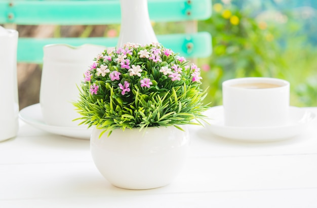 A plastic flower bouquet in a white spherical vase on a morning meal.