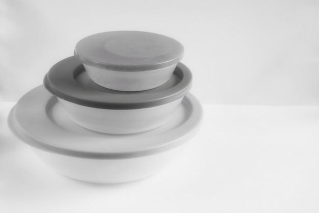 さまざまなサイズのプラスチック製食品容器、白黒写真。