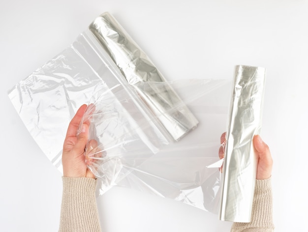 Plastic food wrap for baking products in the oven in women's hand