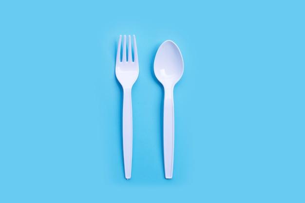 青い背景の上のプラスチックフォークとスプーン。上面図