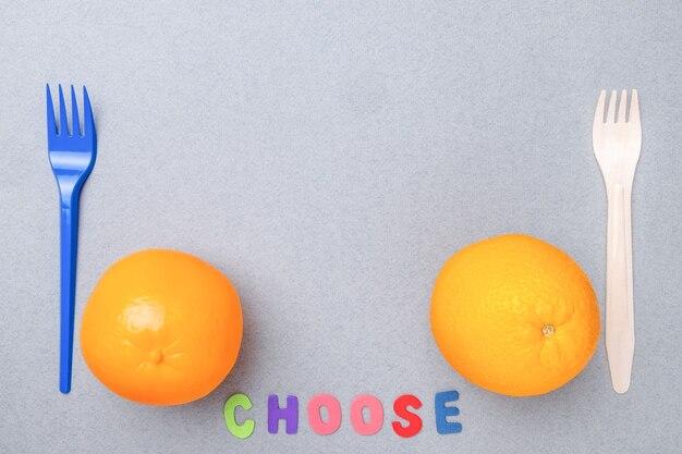 Пластиковая вилка пластиковая игрушка оранжевая деревянная вилка и натуральный апельсин плоской планировки