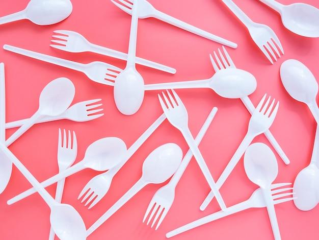 Пластиковые вилки и ложки случайным образом расположены на розовом фоне