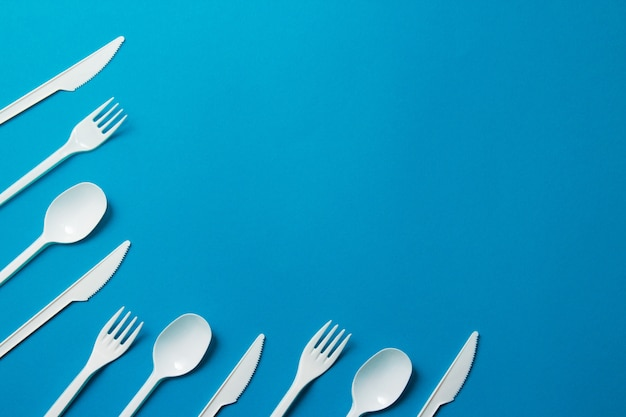 Plastic forks, spoons and knives on blue background