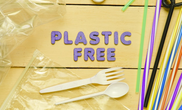 Plastic free concept. many cocktail tubes, plastic spoon, fork, bag, bottle on yellow wooden