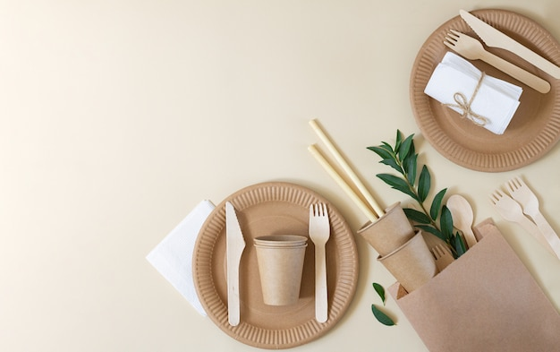 Plastic free and zero waste concept. disposable paper tableware on beige background top view