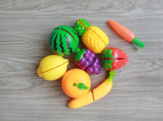 Plastic fruits on wood background, children's toy
