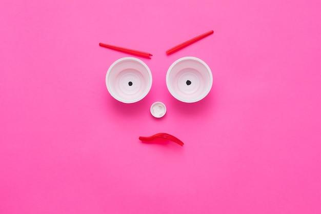 Пластиковый мусорный монстр угрожает экологии. сердитое лицо как композиция на розовом фоне.