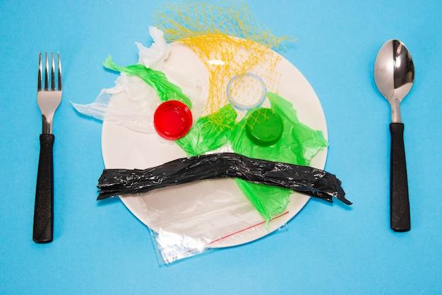 포크와 숟가락 환경 오염 개념 옆 접시에 플라스틱 쓰레기