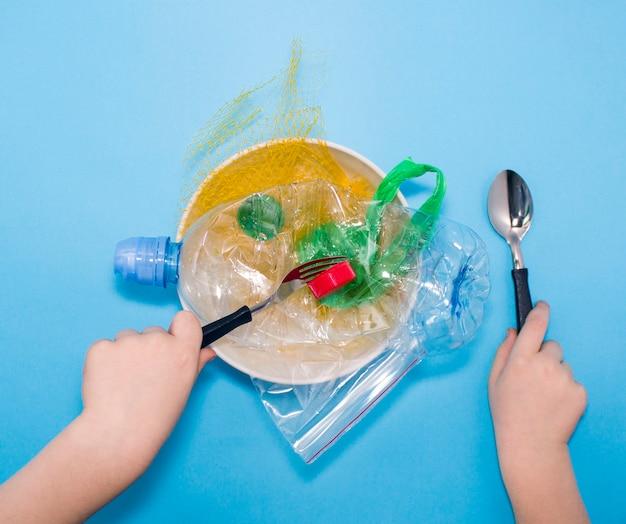 접시에 플라스틱 쓰레기, 포크와 숟가락을 들고 먹는 아이의 손. 개념 환경 오염, 플라스틱 오염.
