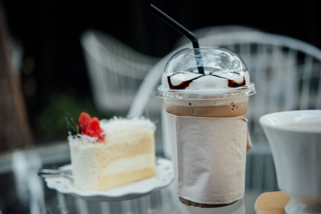 Plastic glass of iced coffee with cake on table in coffee shop