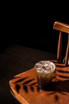 Пластиковый стакан холодного кофе с газированной водой на столе
