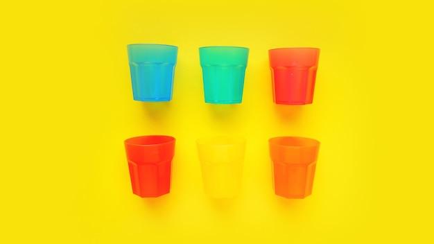 노란색 표면에 절연 다양 한 색상의 플라스틱 유리-디자인 및 배너에 대 한 밝은 여름 개념