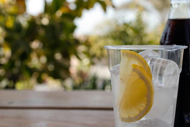 Пластиковый стакан со льдом и ломтиками лимона на деревянном столе, размазанный зеленью на фоне копирование пространства