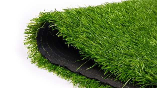 Plastic grass, artificial turf for sports grounds close up.