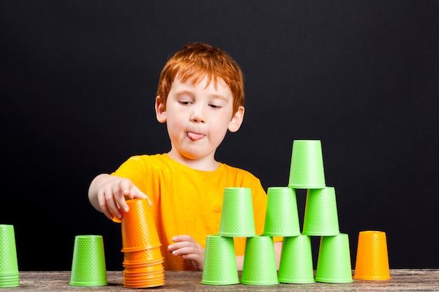 子供がゲーム中に組み立てたプラスチック製の緑とオレンジ色のカップ、プラスチック製の使い捨て食器は、遊びや娯楽、クローズアップのために男の子によって使用されます