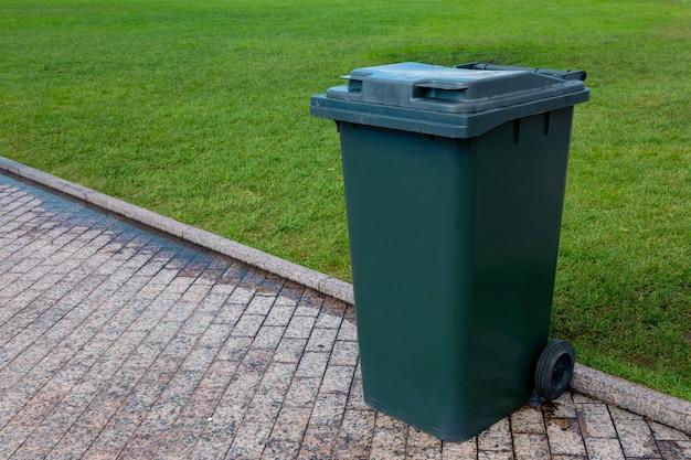 Пластиковая корзина для мусора на зеленых колесах у дороги для сбора мусора. крупный план