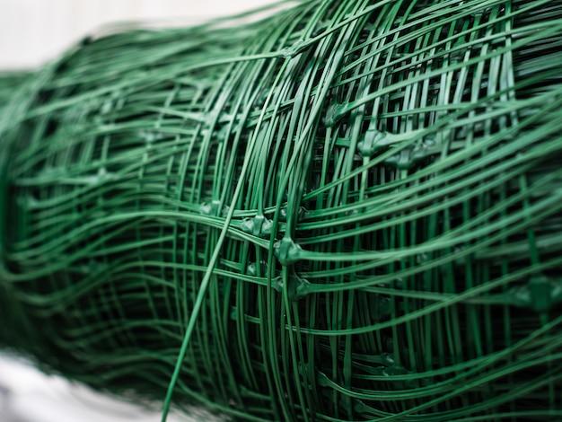 プラスチック製のグリルは緑色です。フェンスの構築でさらに使用するためのロールメッシュ