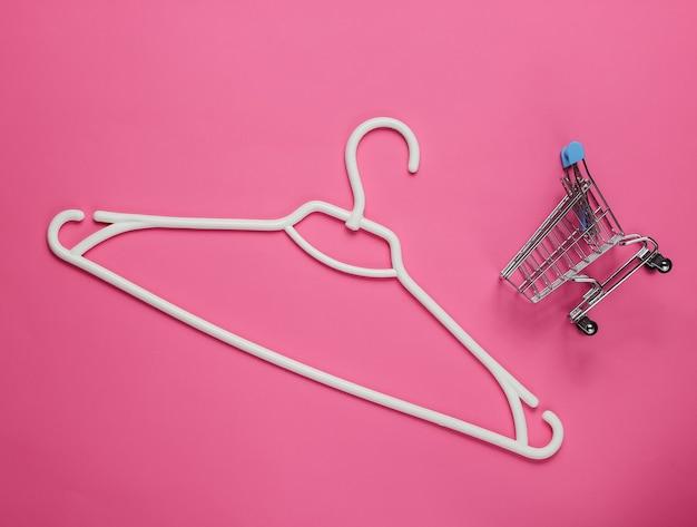 분홍색 종이에 플라스틱 옷걸이와 쇼핑 트롤리