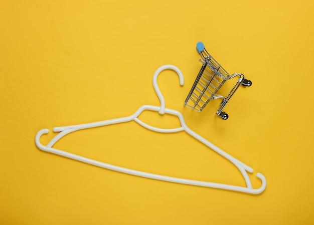 노란색 종이에 플라스틱 옷걸이 및 쇼핑 트롤리
