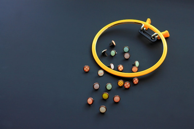 Plastic hoop for embroidery and buttons for clothes on a black background needlework concept