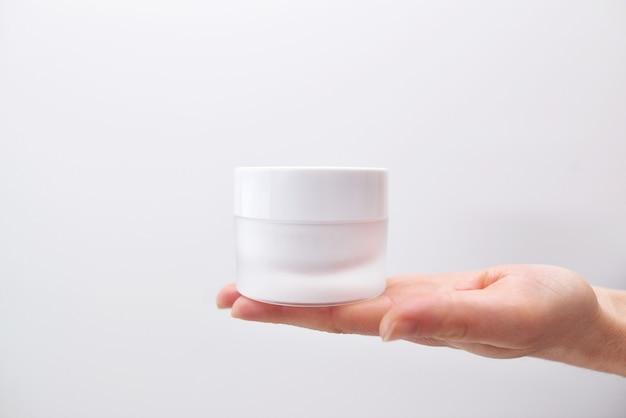 화이트 절연 여성 손에 크림의 플라스틱 항아리. 피부 젊음을 회복시키는 전문 화장품, 노화 방지 크림. 스킨 케어 개념.