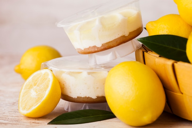 Plastic jar with lemon cheesecake mousse dessert with raw lemons in bamboo basket on light marblebackground