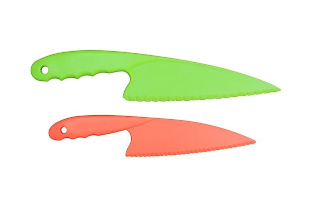 白い背景のクリッピングパスに分離されたプラスチックナイフ緑とオレンジ