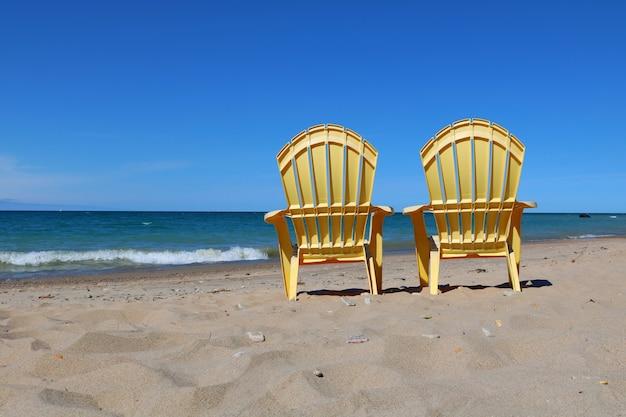 Plastic lawn chairs on a sandy beach