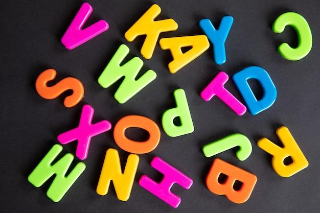 Пластиковые буквы разбросаны по деревянному столу