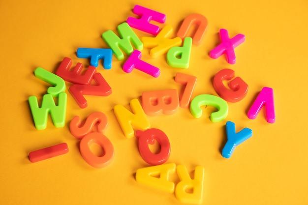 オレンジ色のテーブルにプラスチックの文字が散らばっている