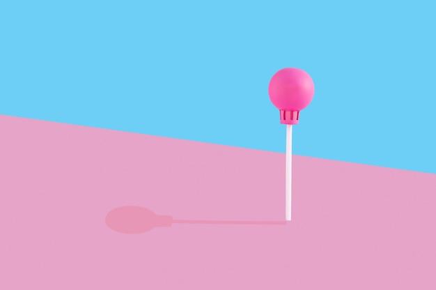 ピンクとブルーの壁にプラスチック製のロリポップ