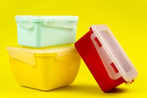 Пластиковые ланч-боксы на желтом фоне, вид сбоку емкости для еды разных форм и размеров