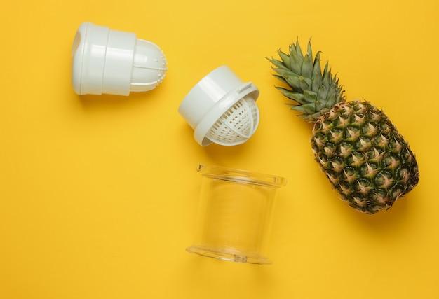 黄色の背景にプラスチック製の手動ジューサーとパイナップル。健康的な栄養、減量の概念。絞りたてのジュース。上面図