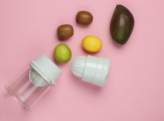 ピンクのパステルカラーの背景にプラスチック製の手動ジューサーとトロピカルフルーツ。健康食品のコンセプト。絞りたてのジュース。上面図