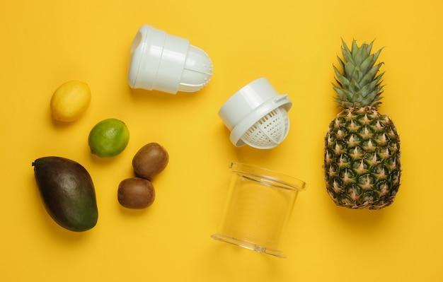 黄色の背景にプラスチック製の手動ジューサーとトロピカルフルーツ。健康食品のコンセプト。絞りたてのジュース。上面図