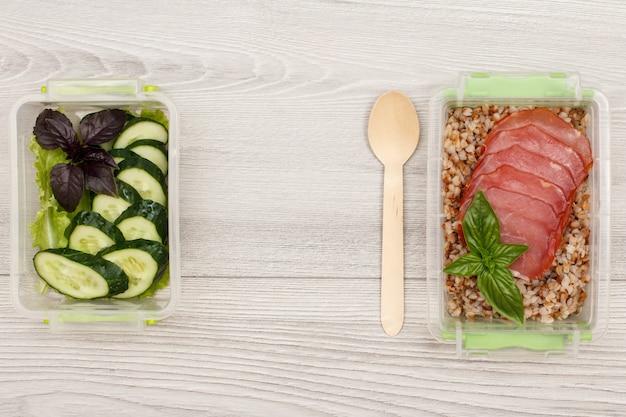 新鮮なカットきゅうりとサラダ、ゆでそば粥、灰色の木製の背景に肉と木のスプーンのスライスが入ったプラスチック製の食事準備容器。コピースペースのある上面図