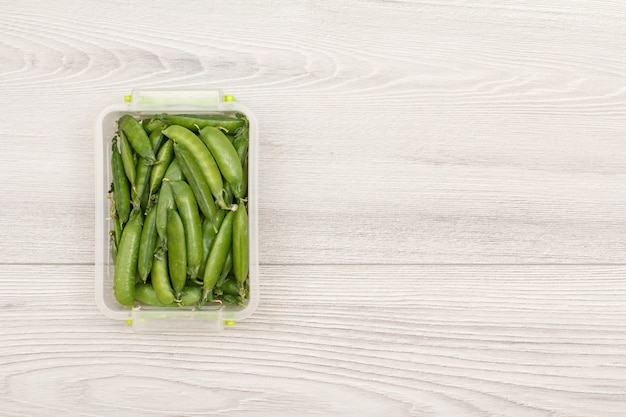 Пластиковые контейнеры для приготовления еды со свежим зеленым горошком на сером фоне. вид сверху с копией пространства.