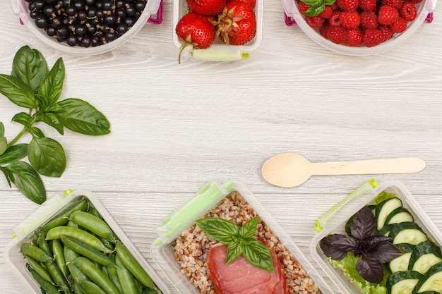 Пластиковые контейнеры для приготовления еды с отварной гречневой кашей из зеленого горошка и кусочками мяса