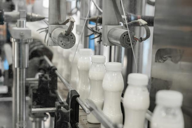 Пластиковые молочные бутылки на конвейерной ленте. оборудование на молочном заводе