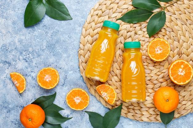 Plastic mini bottles of organic fresh orange juice with raw oranges and tangerines