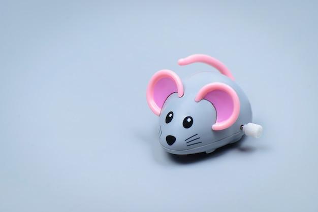 Пластиковая мышка-игрушка на серой поверхности