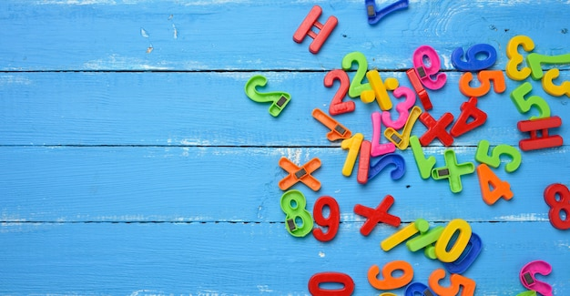 Plastic numbers with magnet scattered on blue wooden background, top view, copy space