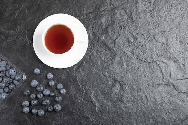 Confezione di plastica di deliziosi mirtilli freschi con una tazza di tè caldo