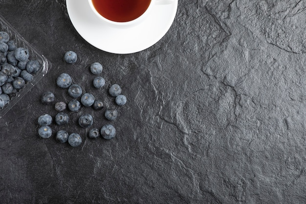 Пластиковый пакет вкусной свежей черники с чашкой горячего чая