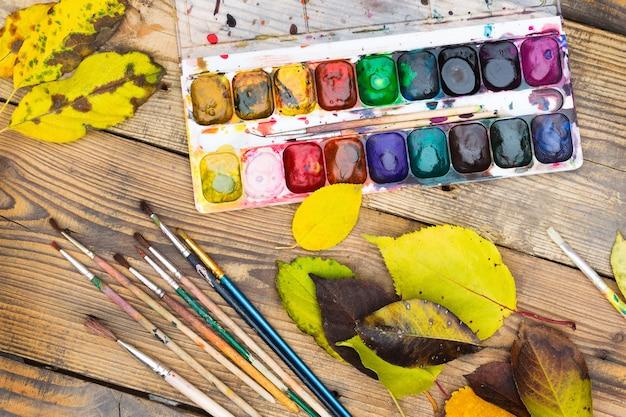 Пластиковая палитра красок с краской, кистями и желтыми листьями на деревянном столе