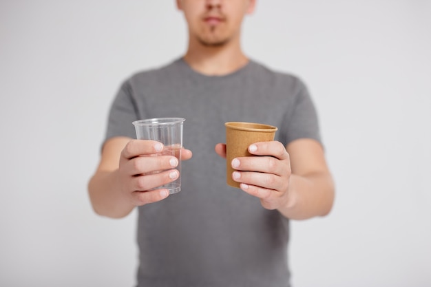 Plastic or paper - man choosing between plastic cup and eco-friendly paper cup over grey background